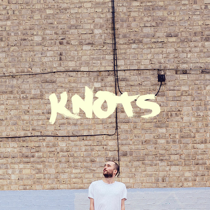 Jake stands in front of a wall again. It says 'Knots' above him.